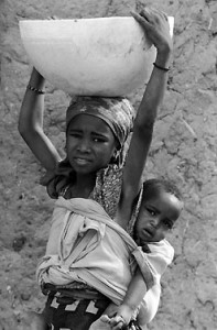 African girl carries water back to her village. A photo by Gil Garcetti in the Water is Key exhibition.